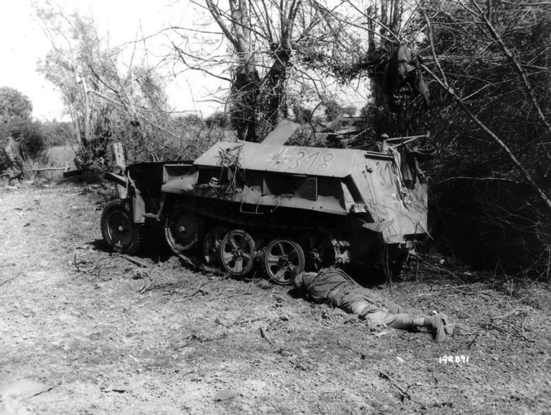 "Aftermath of bombardment of Mortain in front of the station of Mortain-Le-Neufbourg, in the foreground a half-track vehicle Sdkfz of the 2.SS-Panzer division ""Das Reich"", in the foreground the corpse of a dead German soldier."