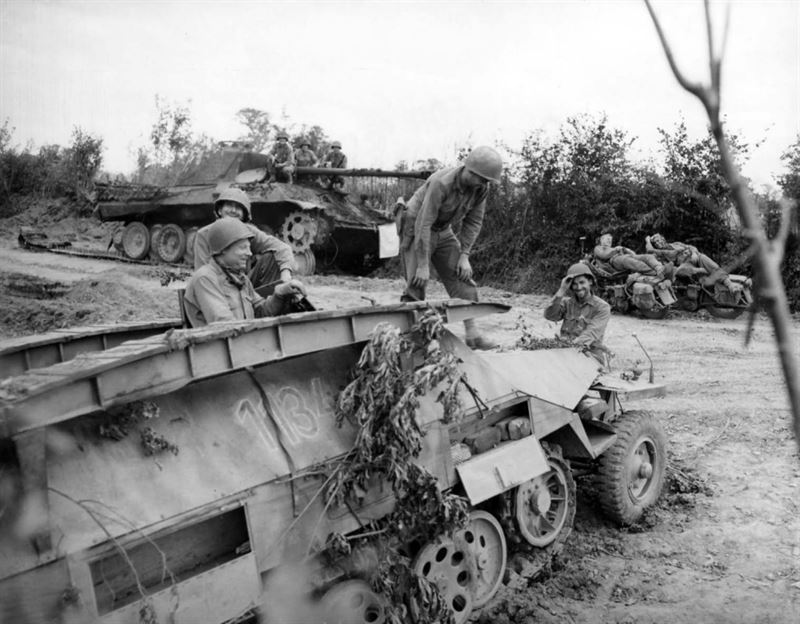 German remains of a Panther tank and SdKfz 251 vehicle inspected by American soldiers somewhere in Normandy.