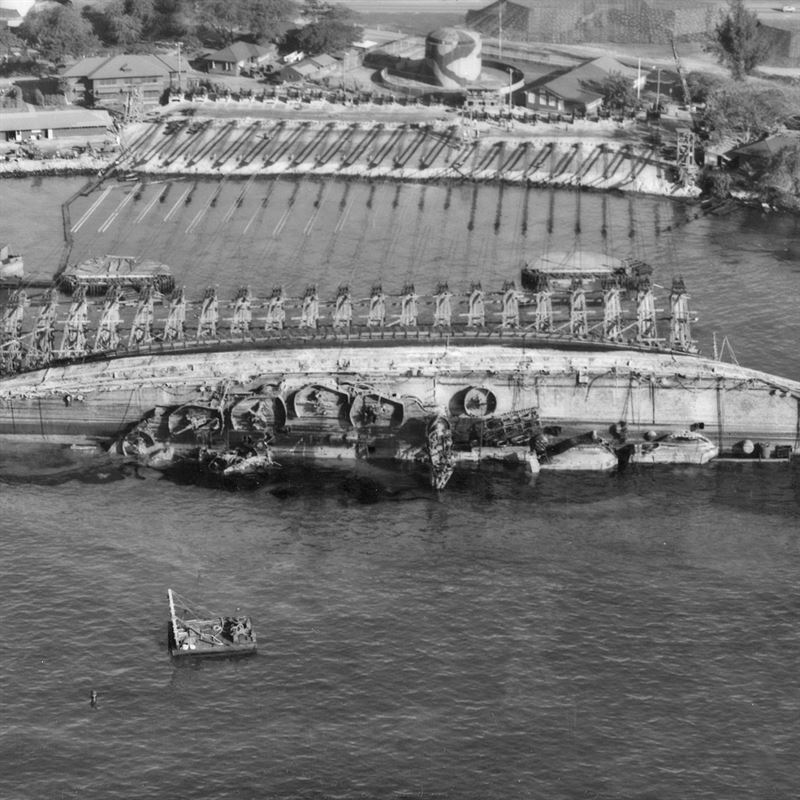 19 March 1943, USS Oklahoma salvage. Aerial view toward shore with ship in 90 degree position.