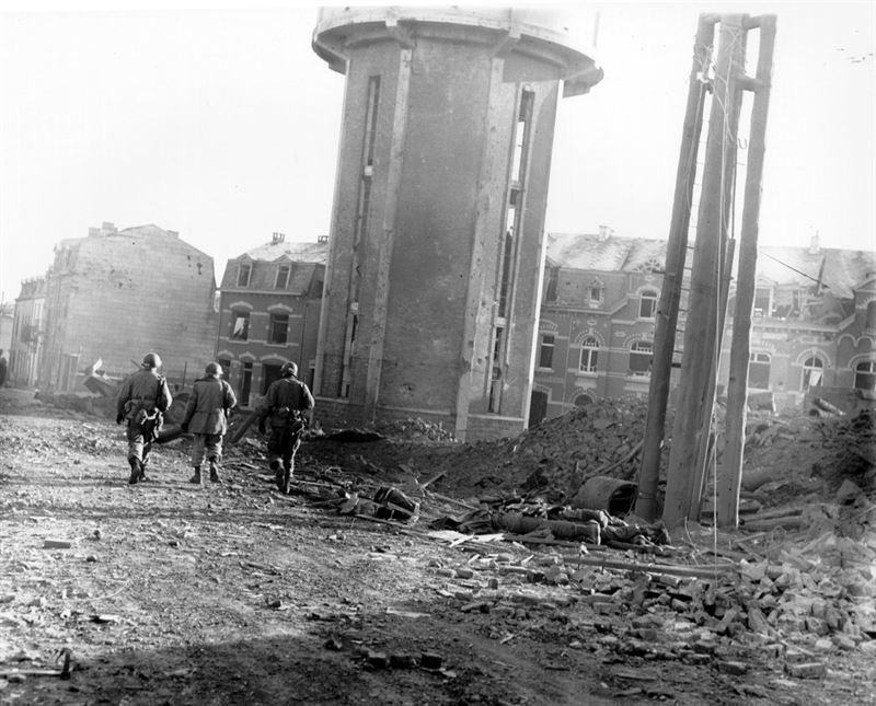 Members of the 101st Airborne Division walk past dead comrades, killed during the Christmas Eve bombing of Bastogne, Belgium, the town in which this division was besieged for ten days. This photo was taken on Christmas Day, 1944.