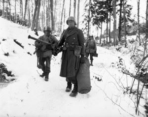 After holding a woodland position all night near Wiltz, Luxembourg, against German counter attack, three men of B Co., 101st Engineers, emerge for a rest.