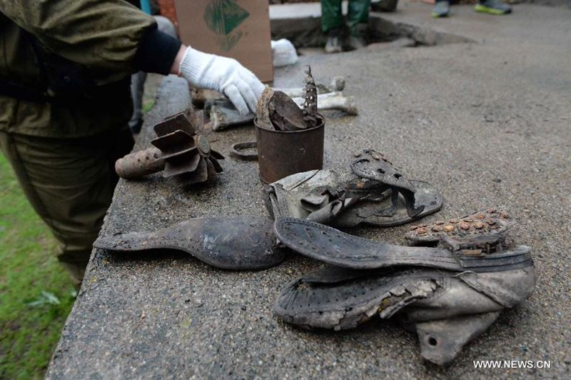 Russian team members demonstrate belongings of WWII Soviet Union soldiers on the Huoshao Mountain in Muling City, northeast China's Heilongjiang Province, May 12, 2015. A one-month-long China-Russia search began Tuesday to locate the remains of Soviet Union soldiers who died in China fighting Japanese invaders in 1945. A 17-member Russian team, along with a group of Chinese archaeologists, are involved in the dig. (Xinhua/Wang Kai)