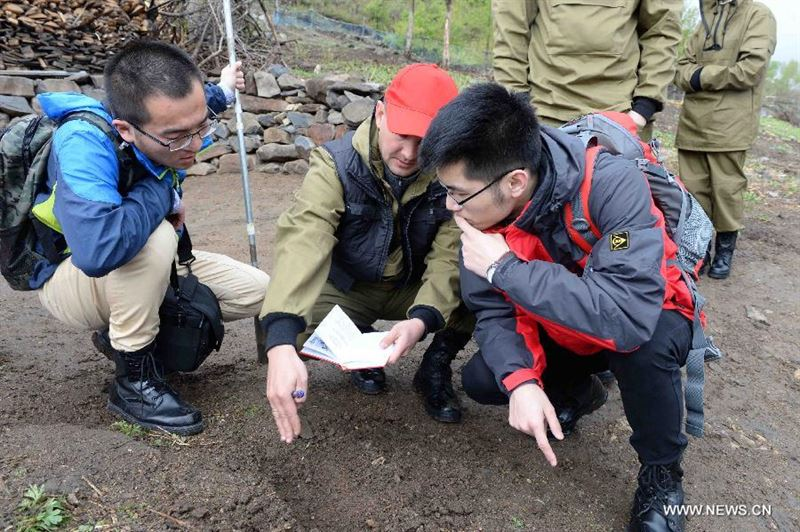 A Russian team member (C) introduces digging techniques to Chinses partners on the Huoshao Mountain in Muling City, northeast China's Heilongjiang Province, May 12, 2015. A one-month-long China-Russia search began Tuesday to locate the remains of Soviet Union soldiers who died in China fighting Japanese invaders in 1945. A 17-member Russian team, along with a group of Chinese archaeologists, are involved in the dig. (Xinhua/Wang Kai)