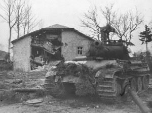"""On Christmas Eve 1944, the 2nd SS Panzer Division Das Reich swept through Manhay and into Grandmenil, pushing aside US Task Force Kane from the 3rd Armoured Division. However, after being pummeled by air strikes on 26 December, the town was assaulted by Task Force McGeorge of the 3rd Armoured Division and taken in the early-morning hours of the 27 by the paratroopers of the 517th Parachute Infantry. This was one of the """"Das Reich"""" Panthers lost in the fighting. It is being inspected by a GI from the 3rd Company, 289 Infantry, 75th Division, which occupied the town on 30 December."""