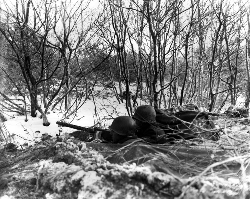 A roadblock is set up with 30 caliber heavy machine gun, and a tank destroyer is ready for action on Adolf Hitler Strasse by the 1st Battalion, 157th Regiment, 45th Division