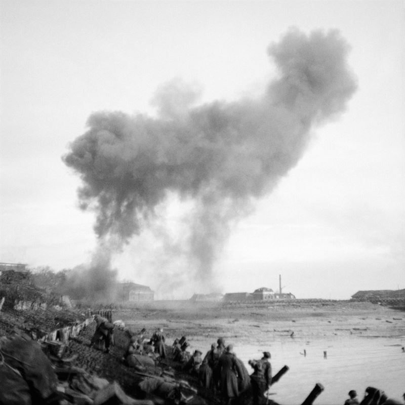 The images show troops advancing along the waterfront near Flushing with shells bursting ahead.