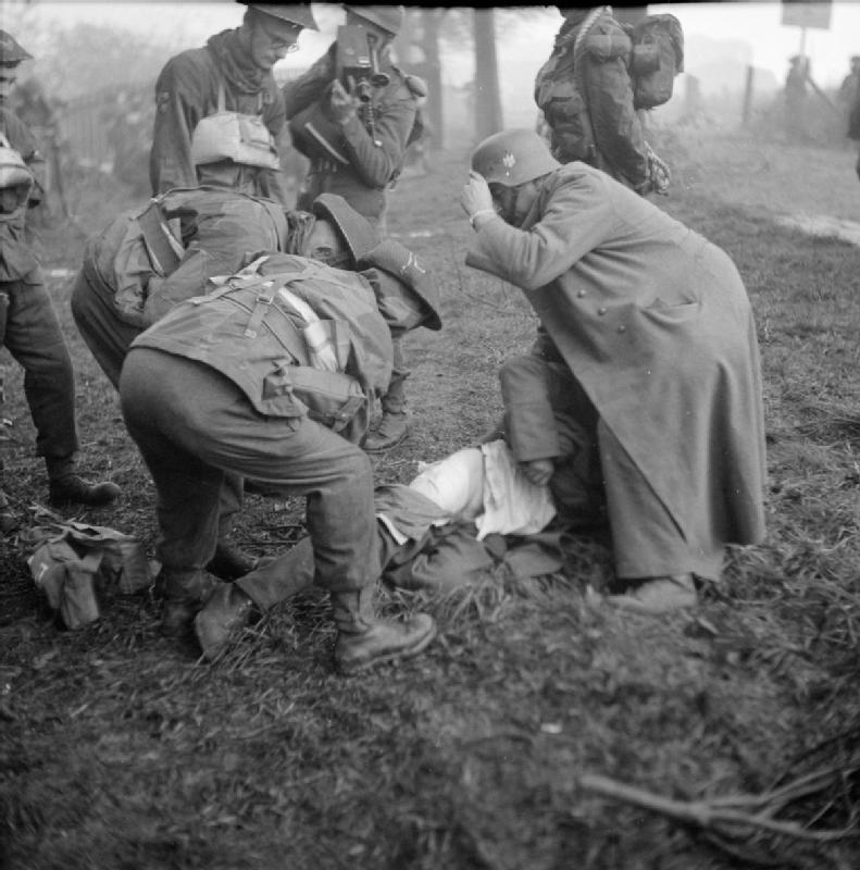 A British medical officer and German POW attend to a casualty during the landings on Walcheren, 1 November 1944. Note the AFPU cameraman filming the incident.