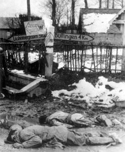 Two dead American soldiers at a road intersection in Honsfeld, Belgium, close to the German border at Losheimergraben, December 17, 1944. The looting of the U.S. soldiers probably points towards the bad state of the German troops during the Battle of the Bulge, as it was common to use all kinds of Allied equipment due to constant shortages.