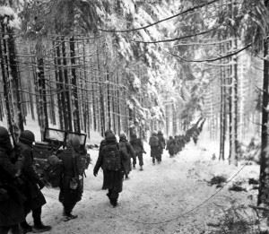 American soldiers of the 289th Infantry Regiment march along the snow-covered road on their way to cut off the Saint Vith-Houffalize road in Belgium on 24 January 1945.