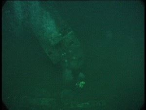 U-155: 50m down the wreck of a submarine comes into view 25m below. Diver Greg Marshall can be seen on the wreck