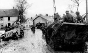 Waffen SS panzergrenadiers move past wrecked American equipment during the 1st days of the Ardennes offensive