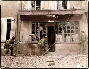 Three soldiers of the 29th US Infantry Division checking deserted buildings in Rue Saint Georges, Saint-Lô. 19th-20th July 1944.