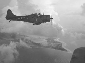 A U.S. Navy Douglas SBD-5 Dauntless dive bomber of bombing squadron VB-5 from the USS Yorktown (CV-10) over Wake Island, 5 or 6 October 1943. Photographed by LT Charles Kerlee of the Naval Aviation Photographic Unit commanded by LCDR Edward Steichen.