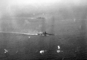 The Japanese battleship Yamato and a heavy cruiser, possibly Tone or Chikuma, in action in the battle off Samar. The photo was taken from an aircraft from USS Petrof Bay (CVE-80). There are three or four U.S. Navy planes visible, one is under fire in the foreground.