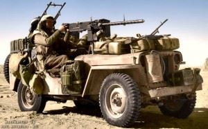 An SAS jeep (Sr/Nº4822478) in the Gabes-Tozeur area of Tunisia. The vehicle is heavily loaded with jerry cans of fuel and water, and personal kit. The 'gunner' is manning the .50 cal Browning machine gun, while the driver has a single Vickers 'K' gun in front, and a twin mounting vickers behind. 1943.