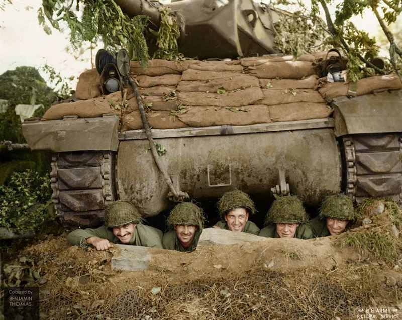 A US tank crew of the 703rd Tank Destroyer Battalion posing for the camera from a foxhole beneath their M-10 tank destroyer, north of Marigny, Normandy on July 26, 1944.