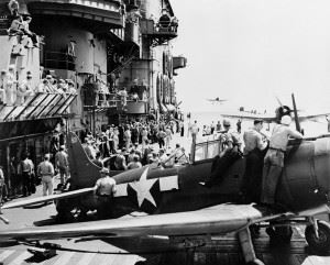 U.S. Navy aircraft from Carrier Air Group 12 (CVG-12) landing aboard the aircraft carrier USS Saratoga (CV-3). A Douglas SBD-5 Dauntless is in the foreground, Grumman F6F-3 Hellcats are landing.