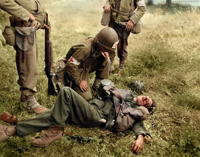 An American medic tends to a seriously injured German soldier who appears unconscious or dead, Normandy, Saint-Lo, June 1944