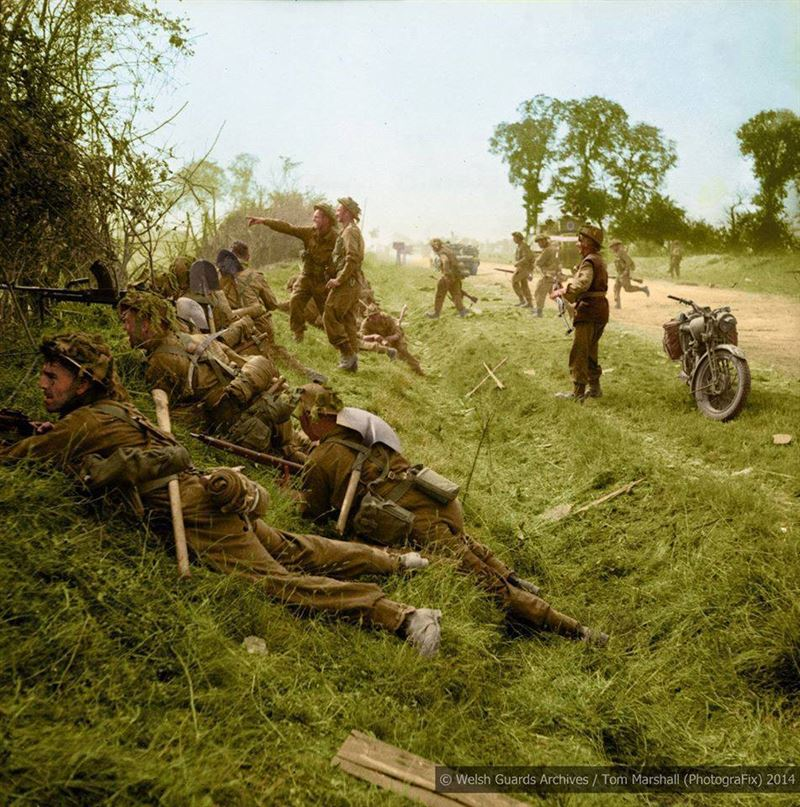 Cagny, Caen, Normandy during 'Operation Goodwood'. The Company Commander, Maj J. D. A. Syrett, is seen indicating a mortar target to Sgt Vessey. Gdsm Kitchen is in the foreground and Gdsm Fenwick is the Bren gunner. Major Syrett was killed a few days later.
