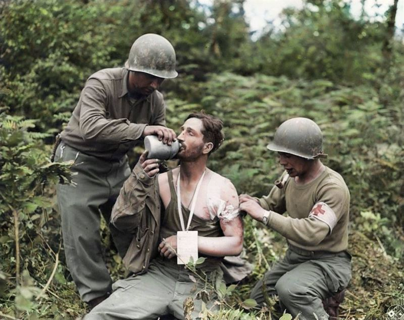 US Medics attend to a wounded GI following the liberation of the village of La Haye-du-Puits in Normandy by the U.S. 79th Infantry Division from German occupation on 9 July 1944.