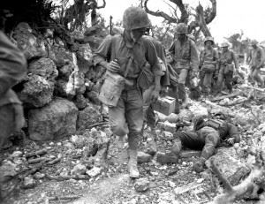 U.S. Marines pass a dead Japanese soldier in a destroyed village, April 1945.