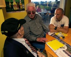 """Airborne veteran James """"Pee Wee"""" Martin, left, shares his experience of his parachute landing during D-Day with Erich Bessoir, a former German Waffen-SS soldier, while amateur historian Bert Brimks translates June 7, 2014, at Omaha Beach, in Normandy, France. The veterans and former enemies, spent the evening together, exchanging experiences and memories of their fight in Normandy, in 1944. (Credits: Alexander W. Riedel)"""