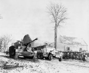 American M3A1 drives past a destroyed German Pz.Kpfw.IV J in Foy, Belgium during the Battle of the Bulge.