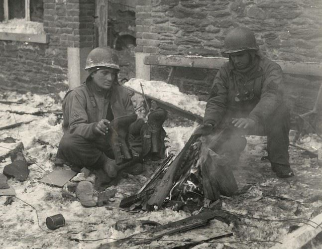 U.S. 3rd Army soldiers thaw out by fire on slush covered street in Foy, Belgium. (Credits: Pininterest)