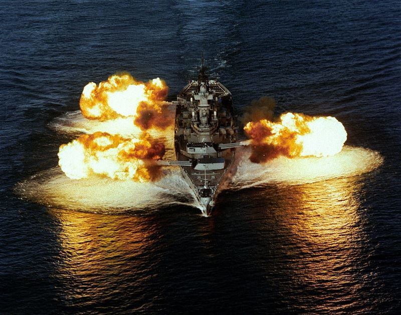Aerial bow view of the Iowa-Class Battleship USS NEW JERSEY (BB-62) firing its nine 16-inch/50 caliber guns simultaneously.