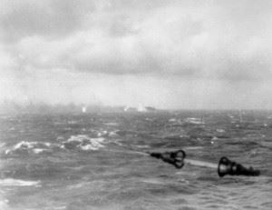 The sinking German battleship Bismarck on fire in the distance, surrounded by shell splashes. The photo was taken from one of the Royal Navy warships chasing. (Credits: IWM)