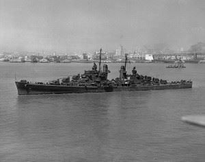 USS Oakland (CL-95) in San Francisco Bay, California, with the San Francisco waterfront in the background, 2 August 1943. (Credits: US Navy)
