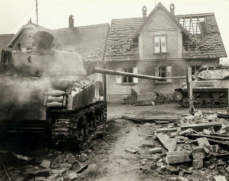 A tank destroyer moving past an American tank that was knocked out during the hot battle when the Americans retook the town. Between the two armored vehicles two medical men are picking up an American soldier that was killed in the fight to take the town.