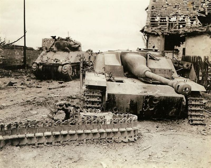 Knocked out American M-4 tank and German Sturmgeschütz IV sit side by side in the street. Note: Hits on the German Stug.