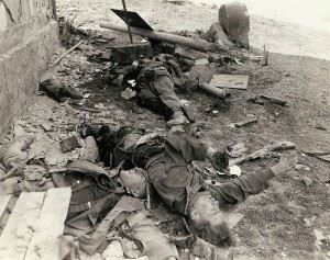 These three dead German Waffen-SS troops were a three man bazooka team that tried to slow up the advance of an American armored column and were killed by a direct hit.