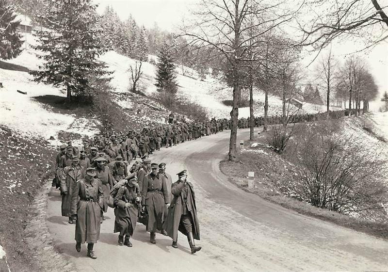 One thousands German officers and men taken in the redoubt mountains are showed being marched back over to the mountain road that they once defended. The road leads to an important Austrian town. Although these officers and men gave up without much resistance, other German troops offered fanatical resistance at key towns along the way.