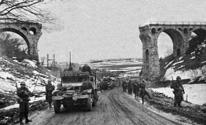 The 1st Battalion of the U.S. 26th Infantry Regiment passing through the railway viaduct north of Bütgenbach, Belgium, on the Monschauer St. (N647) towards Bütgenbach. The railway viaduct was part of the line running from Losheim/Eifel (Germany) to Trois-Ponts, Belgium, and had been blown up by the retreating German troops. (Credits: US. Army Center for Military History)