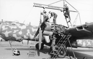 """A He 177 having an engine maintenance overhaul - note the second cylinder's exposed exhaust stub being even with the leading edge, an indication of the rearwards location of the """"power systems"""". (Credits: Bundesarchiv)"""