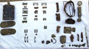 Assorted personal items discovered with the remains of an Australian soldier who died in West Timor in February 1942. The artefacts unearthed include a water bottle, brass fittings from webbing and a haversack, a torch, a comb, a watch and some coins. (Credits: Australian Department of Defence)