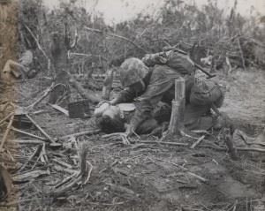 "A Marine wounded in action at Peleliu, gets a drink of water from the canteen of a thoughtful buddy."" (Credits: USMC Archives)"