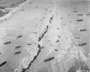 """""""Omaha Beach""""American Liberty ships were deliberately scuttled off the beaches to provide makeshift breakwaters during the early days of the invasion somewhere in France. This scene shows 13 Liberty ships formed into a protecting screen for the vessels unloading on the beach. (Credits: U.S. Army)"""