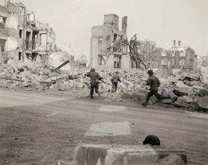 Seventh Army riflemen dash for cover amidst rubble of destroyed buildings in (?) as enemy pours in intermittent artillery, nebelwerfers and small arms fire at advancing yanks (?). Road and rail communications town and key to southern Germany has been bitterly contested by fanatically resisting German forces.