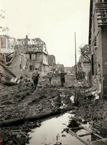 Street by street: Two germans flushed from a house in (?) are marched under guard over battle churned ground. Past razed buildings to the rear and the fighting goes ahead in another street.
