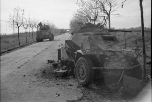 Sherman tanks pass a knocked-out German SdKfz 222 armoured car, 25 January 1944, in Italy. (Credits: IWM)