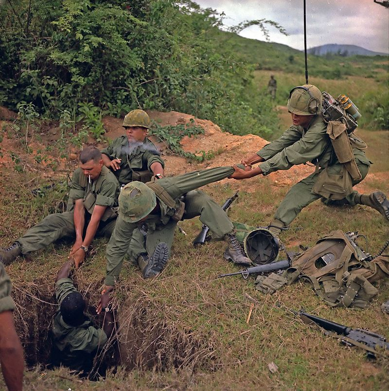 """Operation """"Oregon,"""" a search and destroy mission conducted by an infantry platoon of Troop B, 1st Reconnaissance Squadron, 9th Cavalry, 1st Cavalry Division (Airmobile), three kilometers west of Duc Pho, Quang Ngai Province. An infantryman is lowered into a tunnel by members of the reconnaissance platoon."""