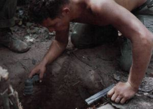 SGT Ronald A. Payne entering a tunnel in search of Viet Cong with a flashlight and M1911 pistol.