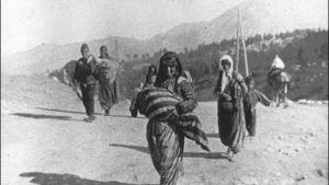 1915: Armenian deportees-women, children and elderly men. Woman in foreground is carrying a child in her arms, shielding it from the sun with a shawl; man on left is carrying bedding; no other belongings or food noticeable among effects being carried. All are walking in the sun on an unpaved road with no means of shelter from the elements. Location: Ottoman empire, region Syria