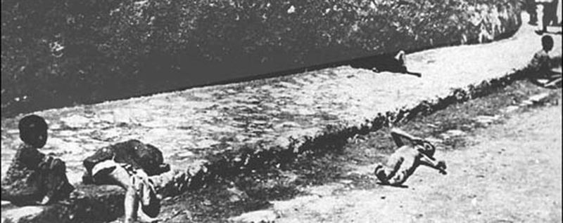 """""""Abandoned and murdered young children of the (Armenian) deportees,"""" according to the photographer, 1915-1916. Three are dead, including a stripped boy in the gutter. Location: Ottoman Empire, Syrian region."""