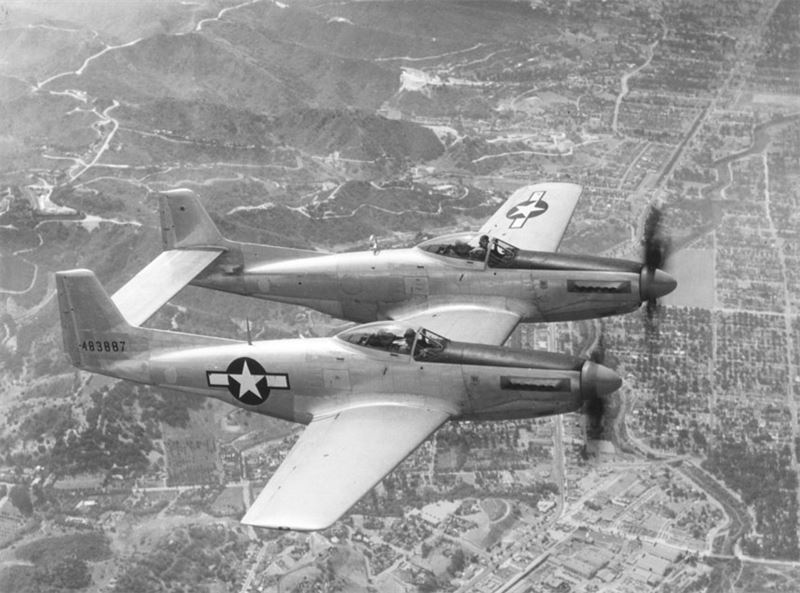 "North American XP-82 ""Twin Mustang"" 44-83887 at Muroc Army Air Base, California. Official flight view of the ""Twin Mustang"", the Army Air Forces long-range fighter. Powered by two 12-cylinder Allison V-1710 engines, the P-82 is capable of a top speed of over 475 miles per hour. Rate of climb for the aircraft is over 5000 feet a minute. Standard armament is six .50 caliber machine guns, but the P-82 can also carry eight additional guns in a special center nacelle."