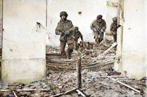 Four men of the 156th Parachute Battalion moving through a shell-damaged house in Oosterbeek, near Arnhem, Netherlands. September 23, 1944.