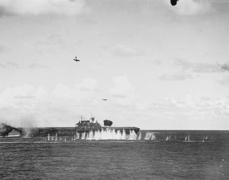 """A Japanese Type 99 Aichi D3A1 dive bomber (Allied codename """"Val"""") trails smoke as it dives toward the U.S. Navy aircraft carrier USS Hornet (CV-8), during the morning of 26 October 1942. This plane struck the ship's stack and then her flight deck. A Type 97 Nakajima B5N2 torpedo plane (""""Kate"""") is flying over Hornet after dropping its torpedo, and another """"Val"""" is off her bow"""
